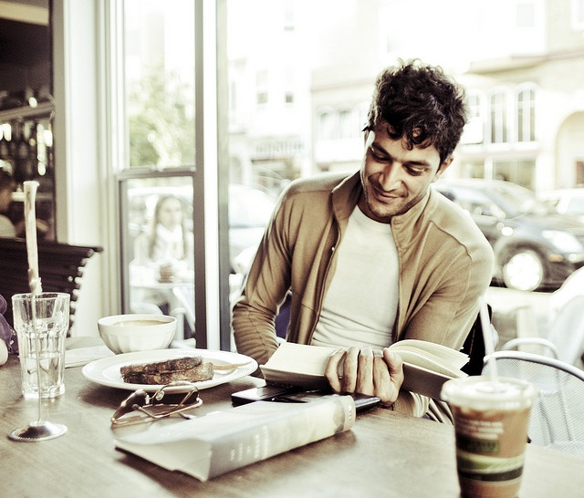 Handsome man in cafe reading book.