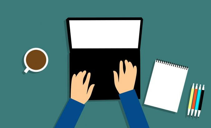 Image of laptop with hands typing, a cup of coffee to one side and paper and pens to the other.